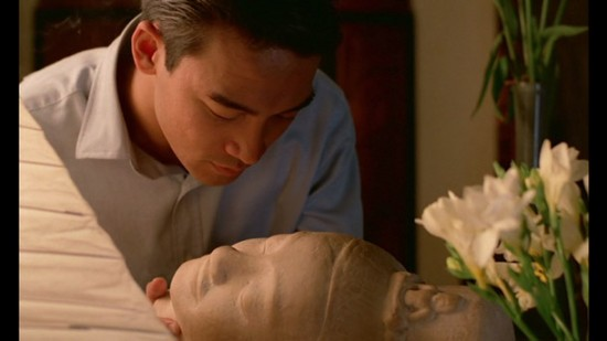 still of Mui's employer holding a bust of the Buddha and looking at the expression