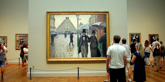 People viewing 'Paris Street; Rainy Day, 1877' by Gustave Caillebotte.